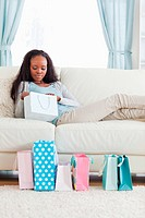Young woman on sofa checking her shopping