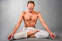 Handsome young man in yoga position. Studio portrait over grey background