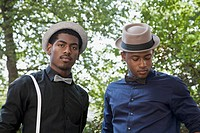 Two young black men dressed in bow ties and hats
