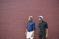 Two handsome young black men walking next to a brick wall