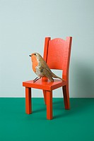 An imitation bird sitting on a miniature chair