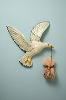 A plastic bird carrying a sack in its beak, hanging on wall