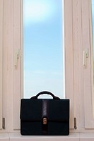 briefcase near a window, behind a window of the dark blue sky