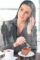 Businesswoman in office cafe enjoying cake and coffee, on mobile phone call, smiling, picture through window, office lobby reflecting.