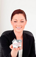 Good looking red_haired woman in suit holding a miniature house while sitting in an office