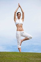 Girl does yoga Tree Pose on hill