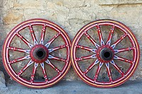 Two decoratively painted wagon wheels leaning against a wall