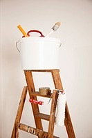 A bucket of paint supplies and paint roller on a step ladder, still life