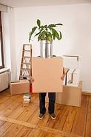 A man carrying a moving box with a plant on top, obscured face