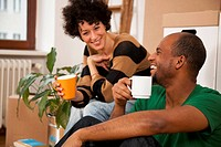 A laughing couple taking a coffee break while moving house, close_up