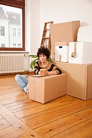 A serious woman taking a coffee break while moving house (thumbnail)