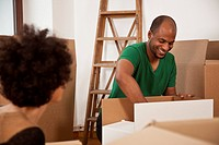 A couple packing moving boxes, focus on man