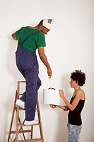 A woman holding a bucket for a man painting a wall with a paint roller