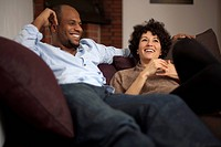 A laughing couple relaxing together on a sofa
