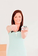 Good looking red_haired female holding a key and a miniature house standing on the floor at home