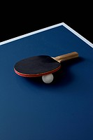 A table tennis bat and ball on a table
