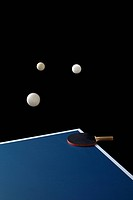 Table tennis balls mid_air and a bat on a table