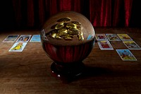 A crystal ball with gold coins in the reflection and tarot cards in background
