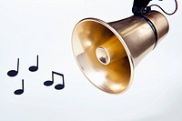 A gold loudspeaker hanging next to musical notes