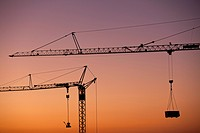 Two construction cranes silhouetted against a sunset sky