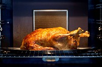 A chicken roasting in an oven