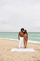 An attractive young couple standing on a beach (thumbnail)