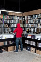 A young man looking through records at a record store, rear view