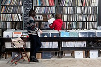 A sales clerk helping a customer in a record store