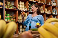 A pregnant woman considering a jar of vegetables at the supermarket