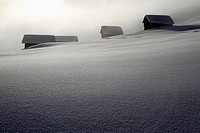 Four log cabins on smooth snowy landscape (thumbnail)