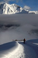 Hiker walking snowy footpath with view of mountain range in background