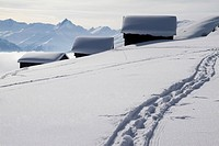 Foot path leading to three snow_capped log cabins