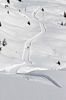 Curved snow path over hills