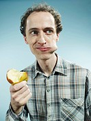 A man with a cheek bulging with a bite of apple, looking to the side