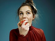 A young hip woman eating an apple