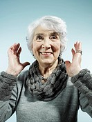 A senior woman with her arms raised in surprise