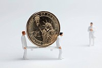 Miniature paramedic figurines carrying a euro coin on a stretcher