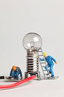 Miniature electrician figurines working on a light bulb