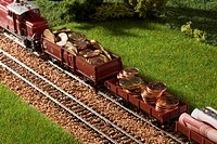A diorama of a miniature train carrying European Union currency (thumbnail)