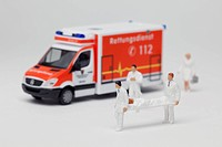 Miniature paramedic figurines carrying a patient on a stretcher from a toy ambulance