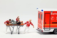 Miniature EMT figurines wheeling a patient on a gurney to a toy ambulance