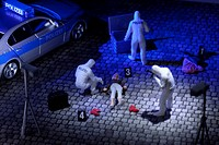 A diorama of a miniature forensics team collecting evidence at a murder scene