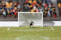 A miniature soccer goalie figurine guarding the goal post