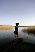 Boy standing at edge of lake