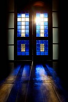 Blue color projected onto floor through stained glass door