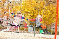 Two girls on swings holding hands (thumbnail)
