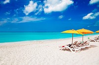Vivid blue of sky and sea with the white sands of Grace Bay Beach, Turks & Caicos, and bright yellow beach umbrellas
