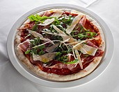 A pizza with ham, rocket, and cheese