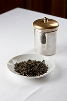 Green tea leaves in a dish next to a canister