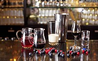 Various glassware with liquids in them next to a cocktail shaker on a bar counter